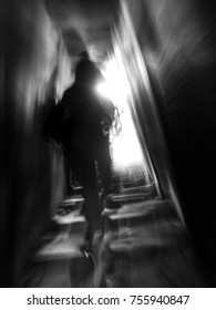 blur unidentified human figure fast moving speed upstairs in a narrow underground staircase escape to bright light exit door with light reflect on the wall for business challenges mood and inspiration