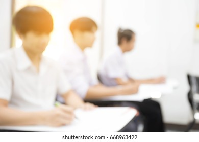 blur university or high school student holding pencil.sitting on row chair writing final exam in examination room or study in classroom.student in uniform.education concept