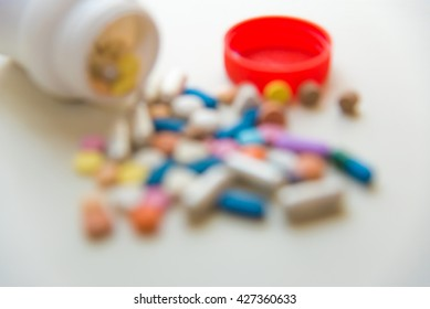 Blur of various medicine pills on white table.
