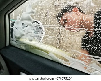blur view of male foreign worker rubbing soap with soft sponge on the car windshield wind screen at a local automotive car-wash center