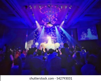 blur wedding party in luxury hotel hall for background with cake and backdrop spot light.
