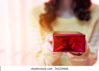blur woman holding a red gift box on Christmas day , selective of gift box.