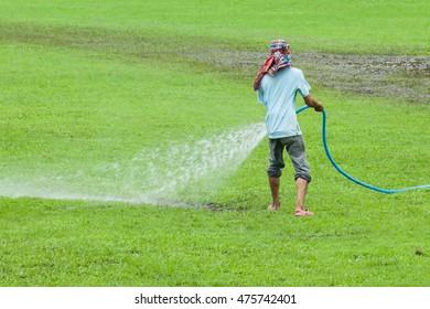 blur of worker preparing  to grass field in football stadium.