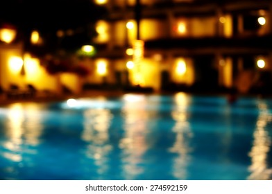 blur yellow golden light reflection in swimming Christmas luxury pool party water at night background