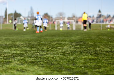 Blur of young boys playing a kids soccer match outdoors on an green soccer pitch.