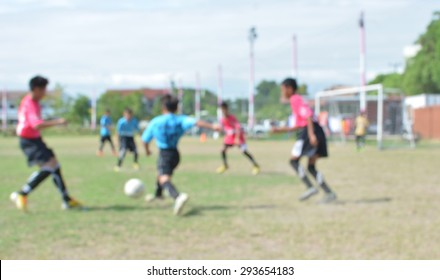 blur young boys playing soccer match on turf.