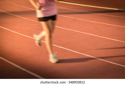 blur young fitness woman running , sunset