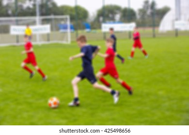 Blur of young kids playing a youth soccer match outdoors on an green soccer pitch.