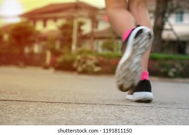 Blur: Young woman running on asphalt