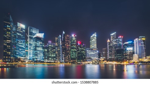 Blured background cityscape at night many tower near lake marsh, swamp at Singapore. blurry too soft