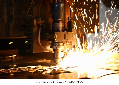 Blured background. Sparks fly out machine head for metal processing laser metal on metallurgical plant. Manufacturing finished parts for automotive production concept