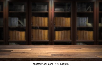 Blured bookshelf in small home library in the background. Table top for product display montage. Dark interior design.