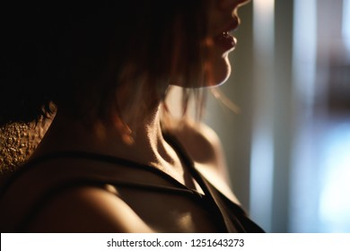 Blured image. closeup portrait of a young beautiful elegant woman in the room with backlight from the window. half of the girls face is covered with hair, woman sensually looks at side.
