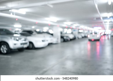 Blured image of Many cars in parking garage interior, industrial building