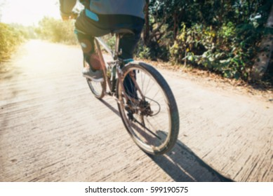 blured low angle view of cyclist riding mountain bike on road at sunrise.
