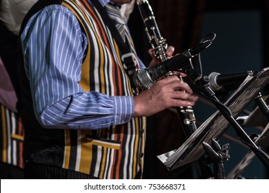 Blured. A musician in a striped waistcoat plays music on the clarinet. Out of focus.