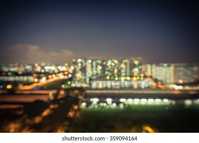 Blurred abstract background aerial view of Eunos neighborhood in Singapore at blue hour. Colorful bokeh from city lights, electric train and car headlights in traffic. Cool vintage tone filtered image
