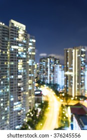 Blurred abstract background aerial view of Toa Payoh neighborhood in Singapore at blue hour. Colorful bokeh from high-rise apartment buildings lights and car headlights in highway. Urban concept