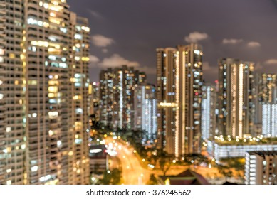 Blurred abstract background aerial view of Toa Payoh neighborhood in Singapore at night. Colorful bokeh from high-rise apartment buildings lights and car headlights in highway. Urban motion concept
