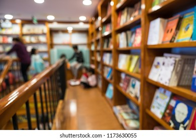 Blurred abstract background of bookshelves in book store, with people finding book in the store.