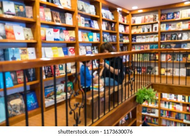 Blurred abstract background of bookshelves in book store, with a girl reading book in the store.