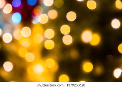 Blurred abstract background of Christmas lights.Brightly glowing yellow-orange balls and lines.Abstract color patterns