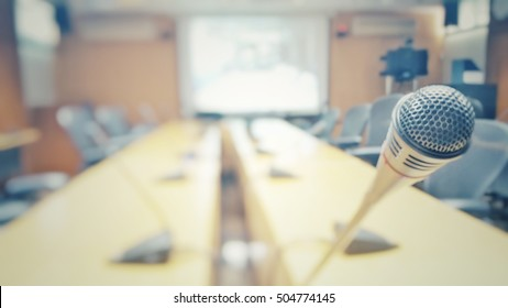 Blurred abstract background of empty projector in conference, meeting room prepare for webinar. Blurry nobody in boardroom, Classroom, Office with chairs and tables with microphone set vintage tone.