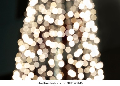 Blurred abstract background with golden glittering christmas lights.