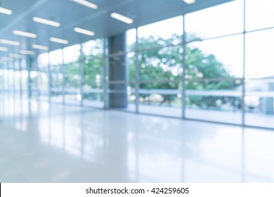 Blurred abstract background interior view looking out toward to empty office lobby and entrance doors and glass curtain wall with frame - blue white balance processing style