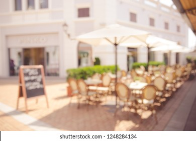 Blurred abstract background of outdoor cafe in Milan, Italy. Outdoor cafe with tables, chairs at the old town.