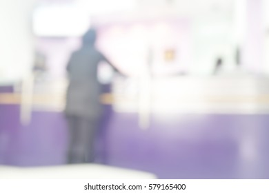 Blurred abstract background of receptionists in counter service center. Blurry view of worker working behind computer monitor in business bank office. Defocused reception payment for electric bill.