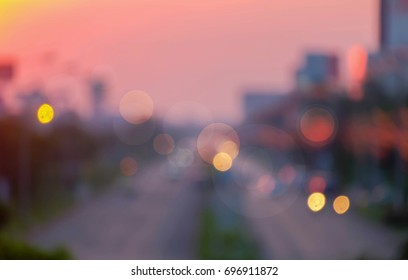 blurred abstract background of the road through small town in the evening sunset.