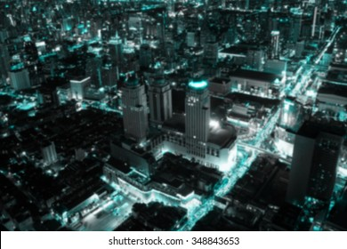 Blurred abstract background of view over cityscape of downtown Bangkok at evening.