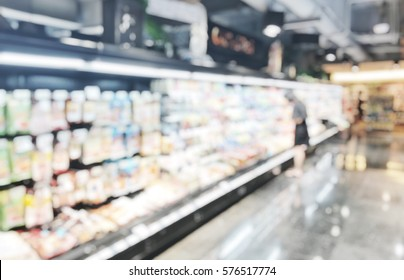 Blurred abstract background woman choosing chilled food product with shopping cart at supermarket. Blurry view colorful chilled deli goods shelves and female shopping with trolley in department store