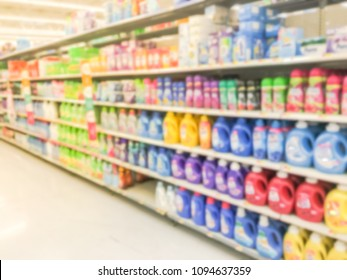 Blurred abstract bleach, fabric softener, laundry detergent, all purpose cleaners shelves in modern grocery retail store. Defocused variety of cleaning, grocery, household aisle from floor to ceiling