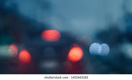 blurred abstract of cars on street in city through front car window