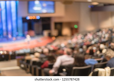 Blurred abstract Christian people inside the church listening to preacher speaking. Defocused back view audience on row of raised sitting chairs looking at stage with large video projector screens