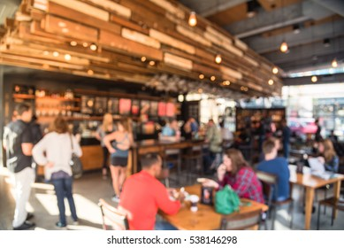 Blurred abstract coffee shop or cafe restaurant in sunny fall morning at Dallas, Texas, US. Blur people, customer waiting for order, pickup and enjoy coffe in bar counter, tables in coffee shop.