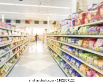 Blurred abstract customer shopping for cookies, candies, snacks, preserved fruits at Asian grocery store in America. Defocused snack time treats aisle on display with price tags at supermarket