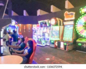 Blurred abstract dark room at entertainment complex in America, motion blurry arcade area with player on car racing simulator machine game