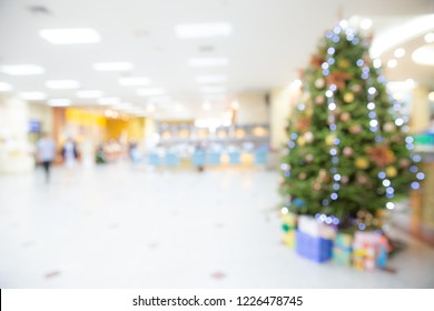 Blurred abstract of decorated Christmas tree with toys, gift box and bauble inside the office building or hospital. Chritmas and Happy New year concept. bokeh lights.