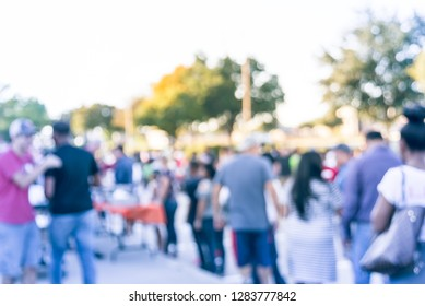 Blurred abstract diverse group of people queuing for free meals at local Church festival near Dallas, Texas, USA. Defocused line of multicultural family members at outdoor food serving line