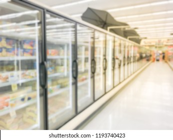 Blurred abstract frozen section at retail store in USA. Defocused huge glass door aisle with variety pack of processed fruit, vegetable, breakfast, appetizer, side, meals, pizza. Food in supermarket