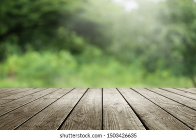 Blurred abstract green bokeh of garden and wooden table background.