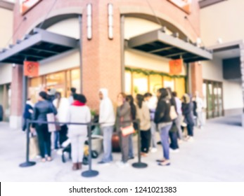 Blurred abstract long line of customer waiting at entrance for fashion store open during Black Friday in outlet mall, Texas, USA. Defocused holiday shopping background, retractable belt stanchion