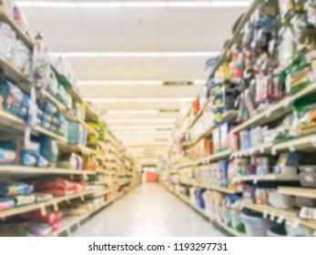 Blurred abstract low angle view dog and cat food shelves at American supermarket. Defocused pet supplies, laundry, dish soap, cat litter, pet and home care aisle row display with price tags