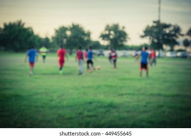 Blurred abstract motion of African American people playing football on green soccer pitch of the park at sunset with warm light at Houston, Texas. Urban healthy lifestyle concept. Vintage filter look.