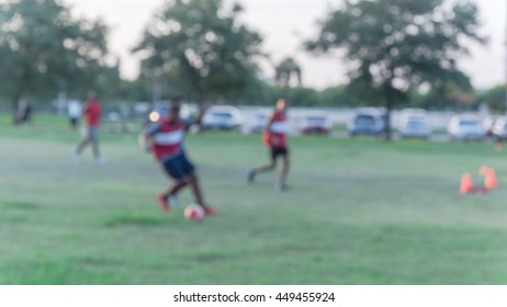 Blurred abstract motion of African American people playing football on green soccer pitch of the park at sunset with warm light at Houston, Texas. Urban healthy lifestyle concept. Panorama style.