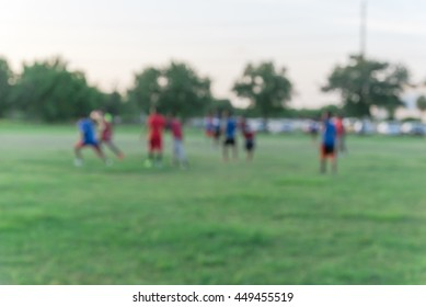 Blurred abstract motion group of African American people playing football on green soccer pitch of the park at sunset with warm light at Houston, Texas. Urban healthy lifestyle concept.