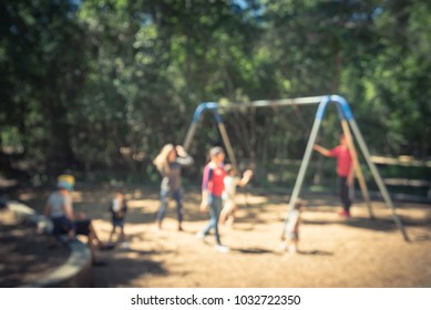 Blurred abstract outdoor playground activities at public park in Texas, America. Children play on swing, kids and parents doing activity together background